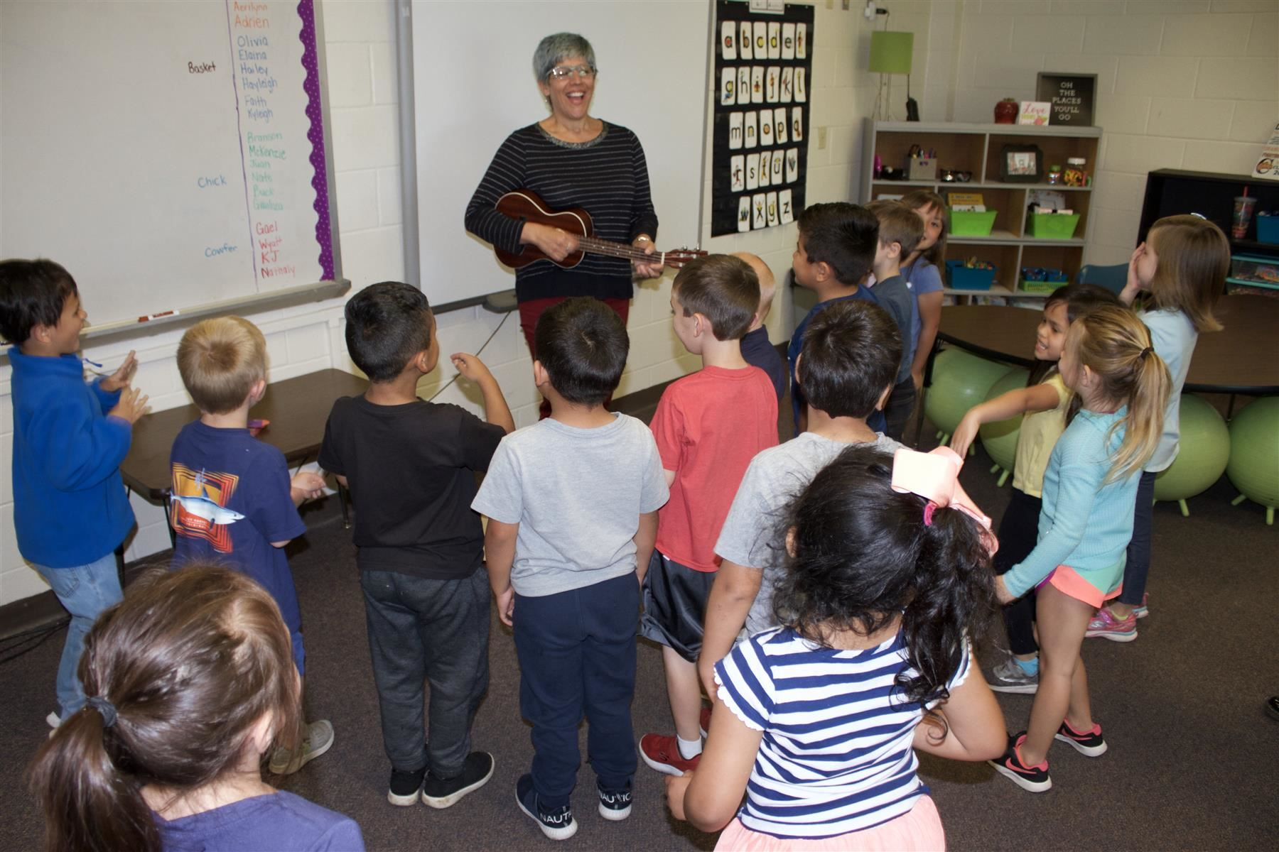 Leslie Cottrell playing her ukulele and singing about the continents with her students.