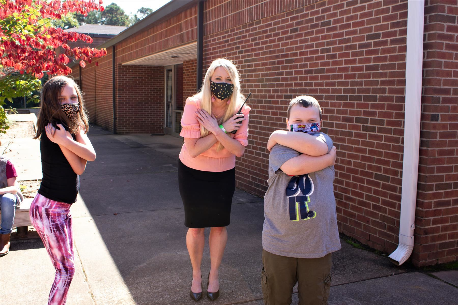 "Duffey and her students demonstrate ""air hugs,"" a creative way to still adhere to the COVID-19 distancing guidelines."