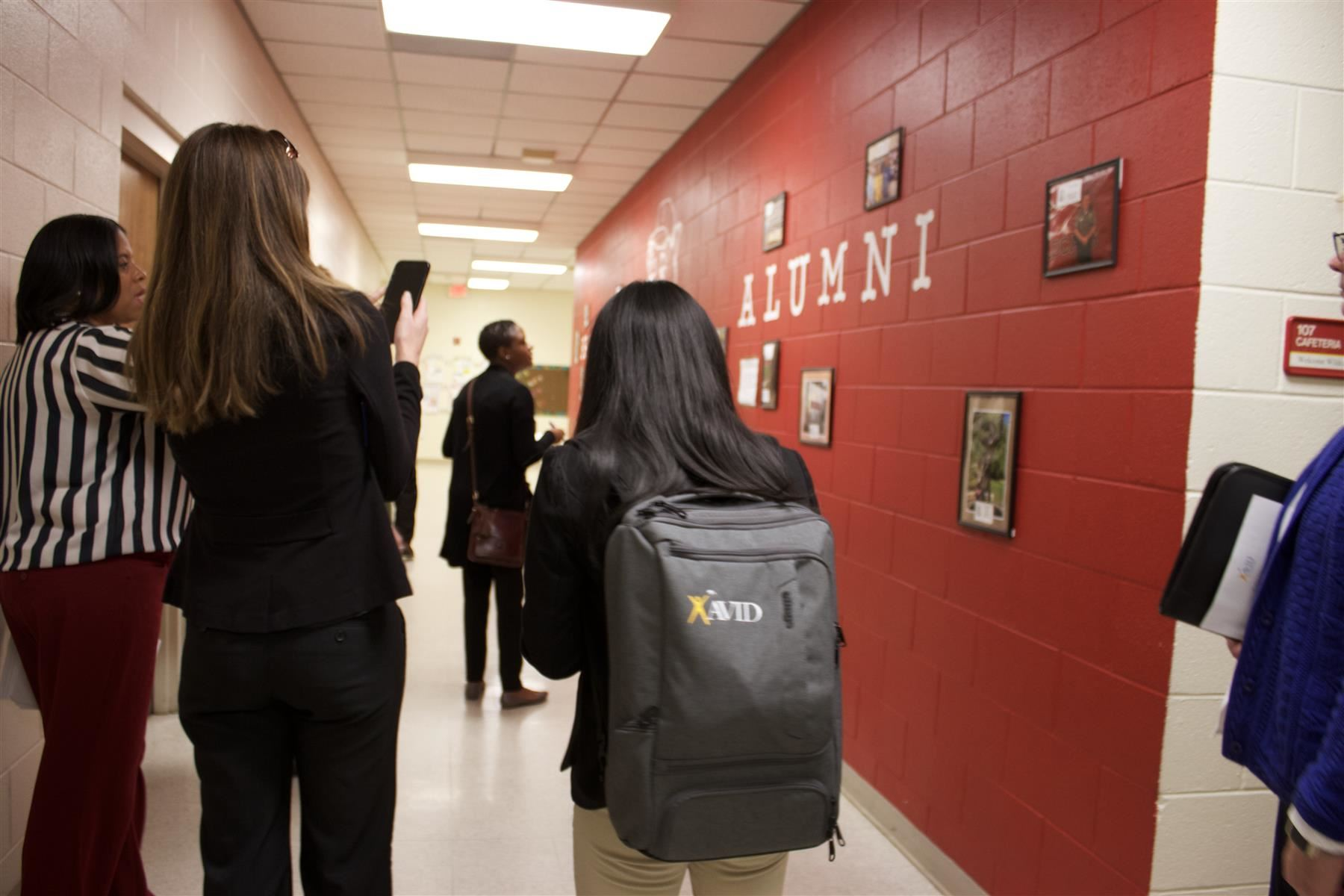 Broadway Elementary students showing visitors their alumni wall.